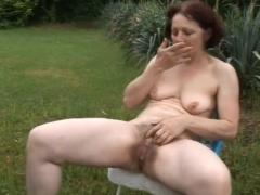 Haarige reife Fotze masturbiert im Garten